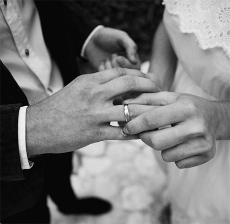 Picture of female putting wedding ring on Male
